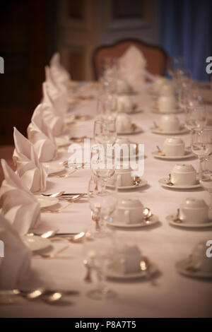 Close-up of a nice long table, laid with a festive table setting; white folded napkins, porcelain plates and cups, glasses and cutlery on a white tabl - Stock Photo