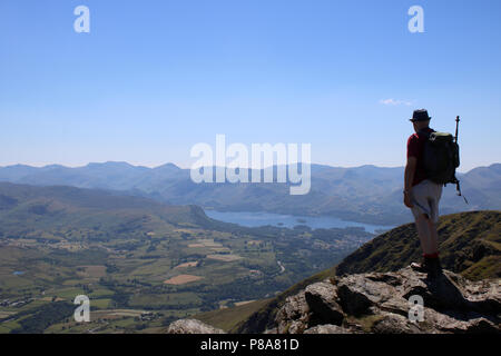 Fellwalker stood at western end of Blencathra (also known as Saddleback) in the Lake District, Cumbria, England looking at the view of Derwentwater. - Stock Photo