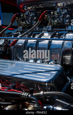 Bright close-up of supercharged Chevy hot rod engine, with lots of color and chrome and those four-barrel carbs sitting on top! Carlisle, PA  2018 - Stock Photo