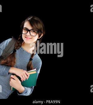 Brunette school girl standing behind the blank board - Stock Photo