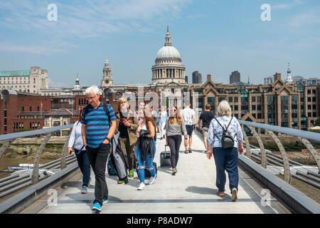 Passengers crossing the London Millennium Footbridge / Millennium Bridge over the River Thames towards St Paul's Cathedral in central London, England - Stock Photo