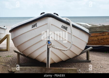 The bow of a small white  boat named Annie resting on supports near the sea shore with the sea in the background at Sidmouth, Devon , England - Stock Photo