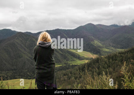 back view of young woman looking at beautiful landscape in mountains, Altai, Russia - Stock Photo