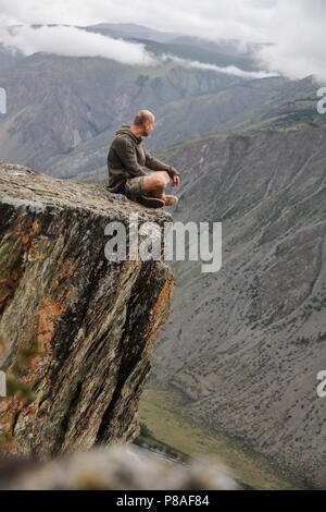 young man sitting on cliff and looking beautiful landscape, Altai, Russia - Stock Photo