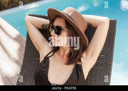young woman in bikini and hat relaxing in sun lounge at poolside - Stock Photo