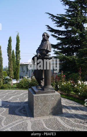 monument to a man of the 18-19th centuries on the square in front of the building, surrounded by flowering flower beds and tall green trees under a bl - Stock Photo