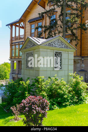 a small decorative building of white stone in front of a huge wooden mansion on a background of bright juicy greens and a blue sky . For your design - Stock Photo