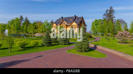 A tiled walking alley leading to a huge wooden house with a black roof and a decorative lake in front of it . For your design - Stock Photo