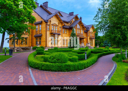 a ramshackle cobbled pathway in a well-kept park in front of a huge wooden mansion among tall green trees and ornamental shrubs . For your design - Stock Photo