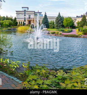 A lovely view of the pond water with a slight ripple on the surface with a fountain in the middle with greenery growing around and a building with a f - Stock Photo