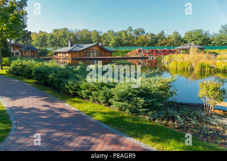 Several wooden houses and other buildings on the shore of a small pond . For your design - Stock Photo