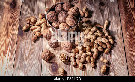 Walnuts and peanuts on a wooden table. Natural sunlight from the window - Stock Photo