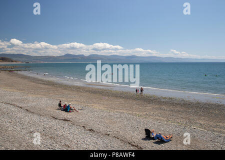Criccieth beach on the Lleyn peninsula in North Wales with extensive views over Tremadog Bay towards the the mountains of Mid Wales in the distance - Stock Photo