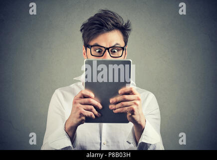 Young man holding tablet in front of face looking amazed and shocked with news standing on gray background - Stock Photo