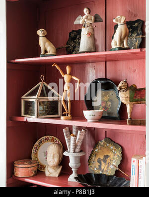 Ornaments and figurines on pink painted shelves - Stock Photo