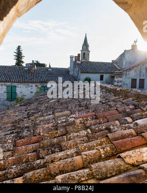 terracotta roof tiles and church spire at sunset, Southern France - Stock Photo