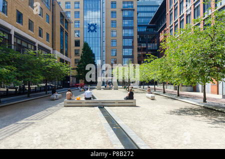 Office workers enjoying the lunchtime sunshine in Oozells Square, Brindley Place, Birmingham - Stock Photo