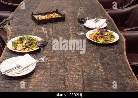 delicious salad with wine on rustic wooden table for romantic dinner - Stock Photo