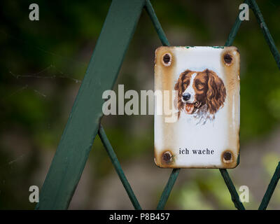 Metal sign with dog saying 'I watch out' on a green fence - Stock Photo