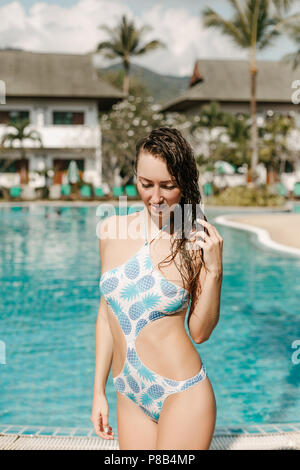 attractive wet girl posing in swimsuit at swimming pool on tropical resort - Stock Photo