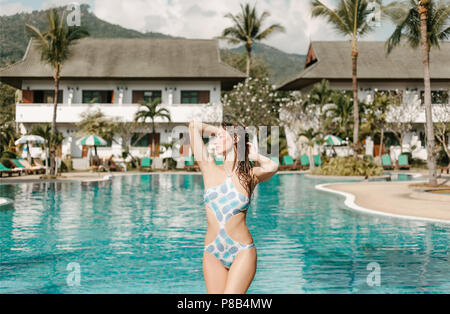 attractive slim girl in swimsuit posing at swimming pool on tropical resort - Stock Photo