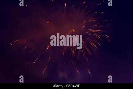 orange fireworks traces in night sky - Stock Photo