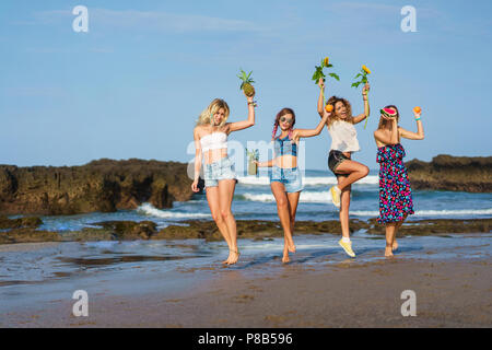 group of happy young women with fruits and sunflowers on beach - Stock Photo