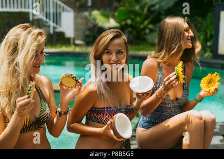 beautiful young women in swimwear holding sliced tropical fruits and flowers near swimming pool - Stock Photo