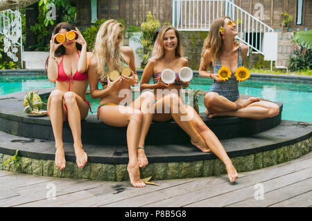 attractive girls in bikinis smiling and holding sliced tropical fruits near pool - Stock Photo