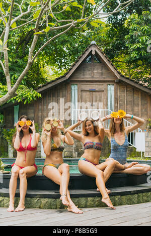 beautiful happy girls in bikinis smiling and holding sliced tropical fruits near pool - Stock Photo