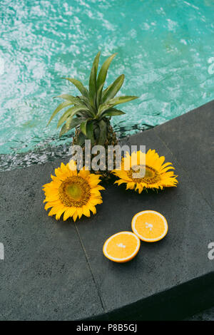 close-up view of pineapple, sliced orange and beautiful yellow flowers at swimming pool - Stock Photo