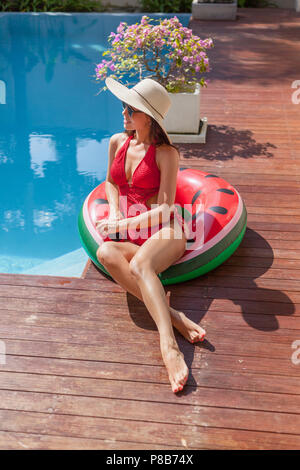 attractive young woman in swimsuit sitting on inflatable ring at poolside - Stock Photo