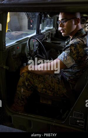 Lance Cpl. Markus Dodd operates a Humvee during a driving course on Camp Kinser, Okinawa, Japan, June 26, 2018, June 25, 2018. Motor Transportation and Maintenance Company conducts regular training for different driving courses including Humvee, government vehicle and assistant driver courses. Dodd, a machine gunner with the Tactical Readiness and Training, G-3, 3rd Marine Logistics Group Headquarters, 3rd MLG, is a native of Niles, Michigan. (U.S. Marine Corps photo by Lance Cpl. Jamin M. Powell). () - Stock Photo