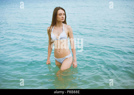 portrait of young pensive woman in bikini standing in ocean - Stock Photo