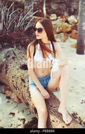 young woman in sunglasses with backpack sitting on fallen palm tree on beach - Stock Photo