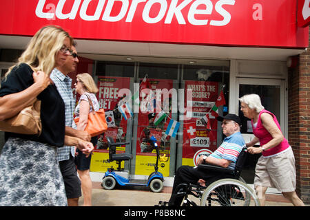 Bognor Regis, Sussex. A woman pushes a man in a wheelchair past Ladbrokes. - Stock Photo