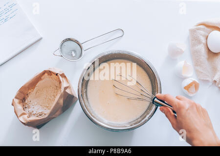 Process of making the dough, woman's hand whips eggs and flour in bowl next to the handwritten recipe and sieve, top view. Flat lay composition of ing - Stock Photo