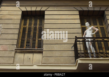 Mannequin on balcony of abandoned house. Spooky doll with human skin tone under peeling white paint. - Stock Photo