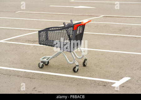 Shopping trolley in the parking lot - Stock Photo