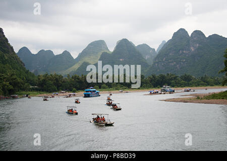 Tourist rafts and cruise boats on the Li River in Guangxi Zhuang china, on the journey from Guilin to Yangshuo. - Stock Photo