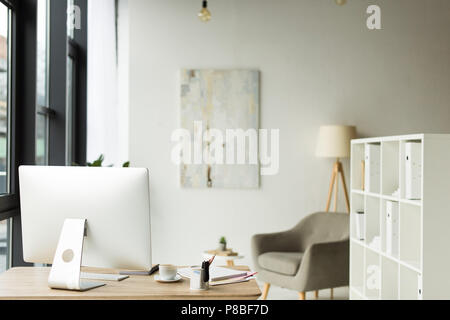 modern office interior with desktop computer and papers on table - Stock Photo
