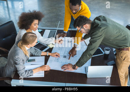 high angle view of african american businessman pointing on something at blueprint in office - Stock Photo
