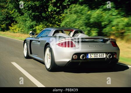 Porsche Carrera GT 2005 model in silver - rare hyper car showing rear view as driving in motion - Stock Photo