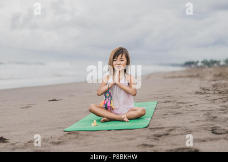 little girl meditating on the beach stock photo 72833457