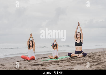 two women and little child practicing yoga on seashore on cloudy day, lotus pose (padmasana) with namaste mudra - Stock Photo
