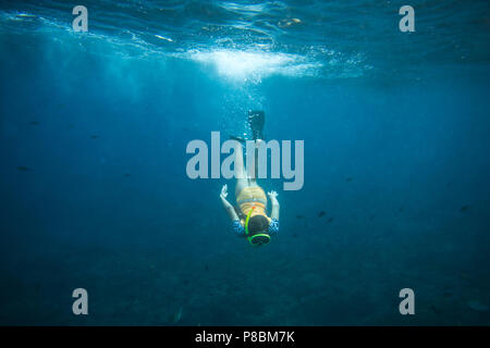 underwater photo of woman in fins, diving mask and snorkel diving alone in ocean - Stock Photo