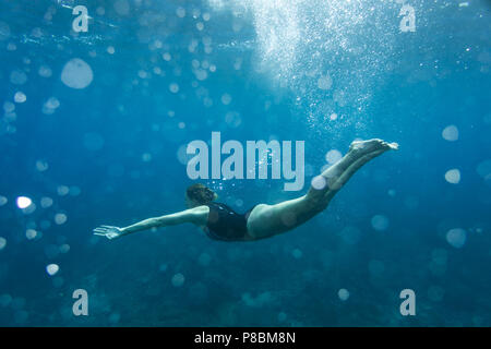 underwater photo of young woman in swimming suit diving in ocean alone - Stock Photo