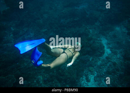 back view of woman in bikini and fins diving in ocean alone - Stock Photo