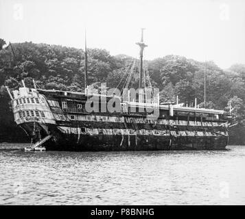 HMS Implacable at Falmouth around late 19th, early 20th century.HMS Implacable was a 74-gun third-rate ship of the line of the Royal Navy. She was originally the French Navy's Téméraire-class ship of the line Duguay-Trouin, launched in 1800. She survived the Battle of Trafalgar only for the British to capture her at the subsequent Battle of Cape Ortegal. In British service she participated in the capture of the Imperial Russian Navy 74-gun ship of the line Vsevolod  in the Baltic in 1808 during the Anglo-Russian War. Later, Implacable became a training ship. - Stock Photo