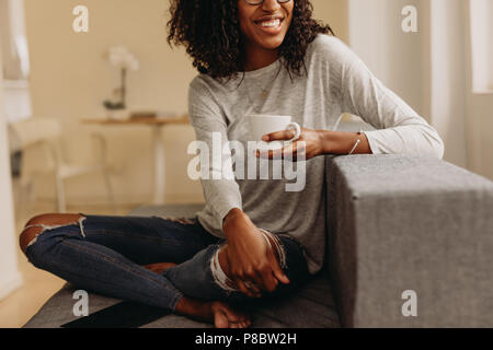 Smiling woman in fashionable torn jeans holding a coffee cup relaxing at home. Woman sitting with legs crossed on sofa at home drinking coffee and loo - Stock Photo